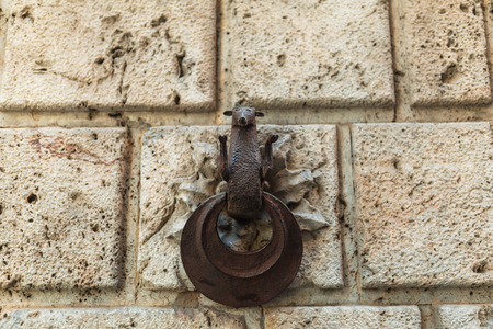 Stone wall with metal statuette decoration in Sienna