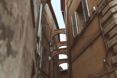 Arch in narrow street in historical quarter of Sienna