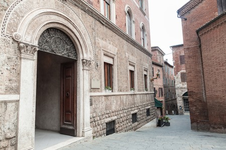 Old arch door in building facade in Sienna
