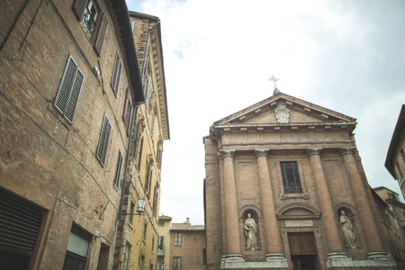 Church of Saint Christopher with statues on facade in Sienna
