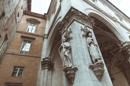 Building facade with statues in historical quarter of Sienna
