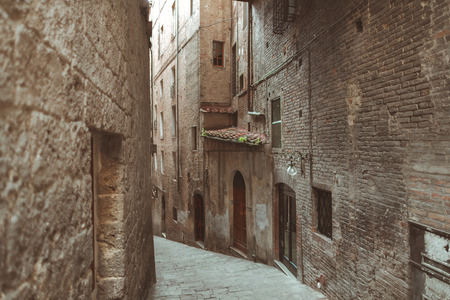 Steep street in historical quarter of Sienna Stock fotó