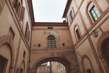 Archway between two buildings in historical quarter of Sienna 写真素材