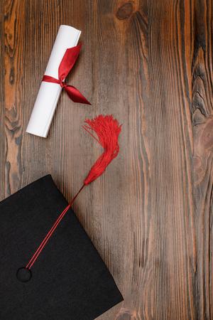 Draufsicht des Diploms und des quadratischen akademischen Hutes auf Holzhintergrund