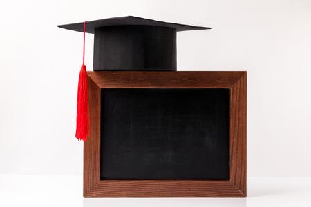 Taza académica en pizarra vacía aislado sobre fondo blanco. Foto de archivo