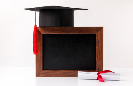 Square academic cup on empty blackboard and diploma isolated on white background