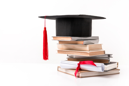 Academic cap on stack of books isolated on white background
