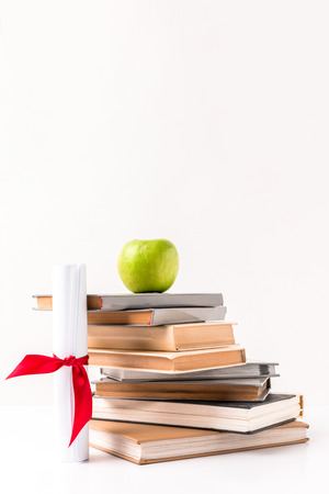Diploma with stack of books with apple on top isolated on white background