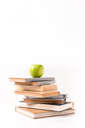 Apple on pile of books isolated on white background Stock Photo
