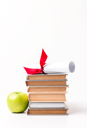 Diploma on pile of books and apple isolated on white background Stok Fotoğraf