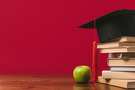 Cropped view of pile of books with academic cap on top and apple on red background