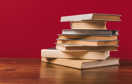 Floor with stack of different books on red background