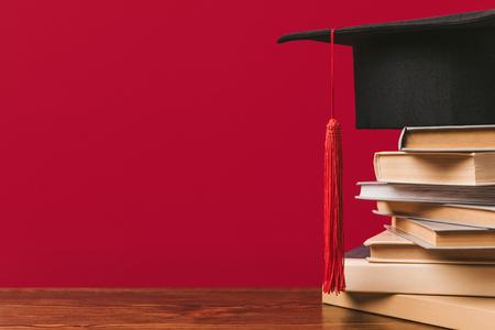 Ausgeschnittene Ansicht eines Bücherstapels mit akademischer Kappe auf rotem Hintergrund