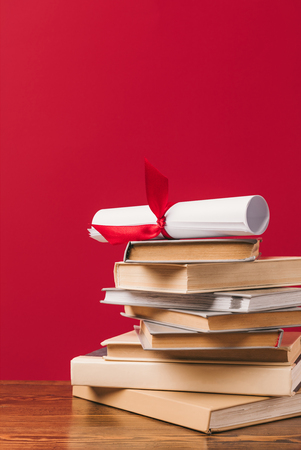 Diploma on top of stack of books on red background