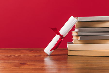 Diploma and stack of different books on red background