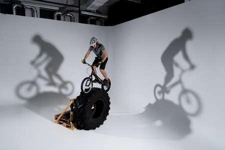 Young athletic trial cyclist balancing on tractor wheel