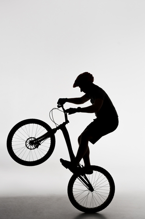Silhouette of trial biker standing on back wheel on white background