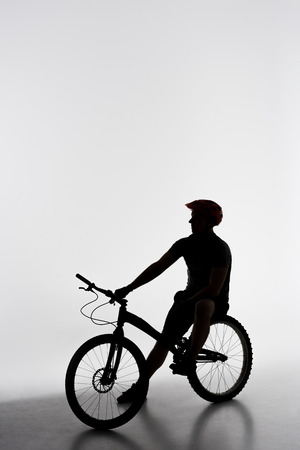 Silhouette of trial biker relaxing on bicycle on white background