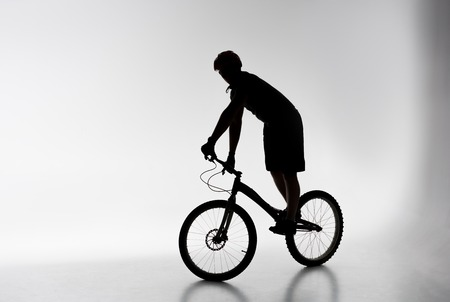 Silhouette of trial cyclist in helmet balancing on bicycle on white background