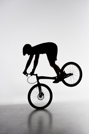 Silhouette of trial biker performing front wheel stand on white background Stock Photo