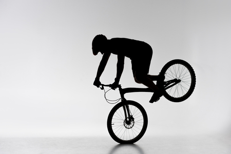 Silhouette of trial cyclist performing front wheel stand on white background