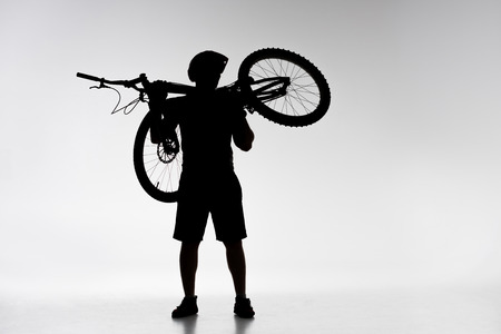 Silhouette of trial biker holding bicycle on shoulders on white background Stock Photo