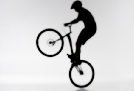 Blurred shot of silhouette of trial biker performing bunny hop on white background Stock Photo