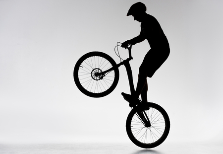 Silhouette of trial biker performing bunny hop on white background Stock Photo