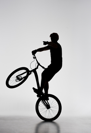 Silhouette of trial biker standing on back wheel and pointing somewhere on white background