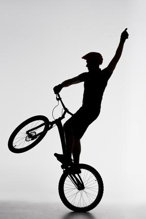 Silhouette of trial cyclist standing on back wheel and raising hand on white background