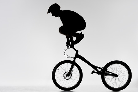 Silhouette of trial biker standing on handlebars with hands on white background
