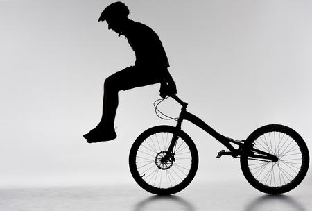 Silhouette of trial biker performing stunt on bicycle on white background