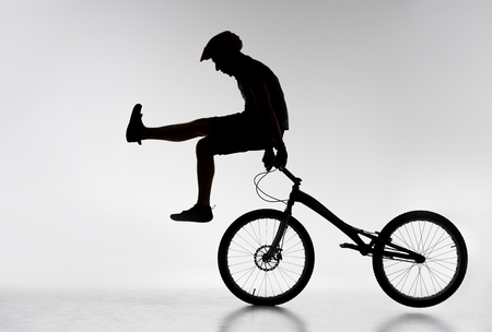 Silhouette of trial cyclist standing on handlebars with hands on white background 免版税图像