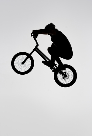 Silhouette of trial cyclist jumping on bicycle on white background