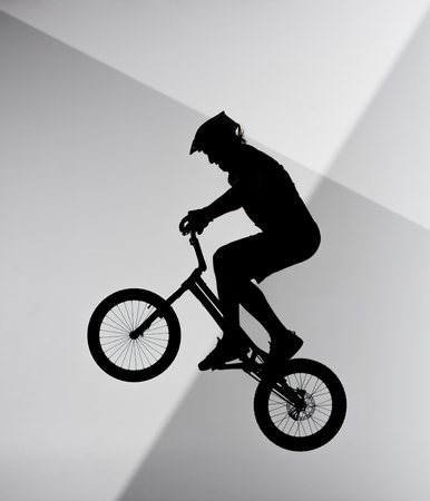 Silhouette of trial cyclist jumping on bicycle on abstract grey and white background