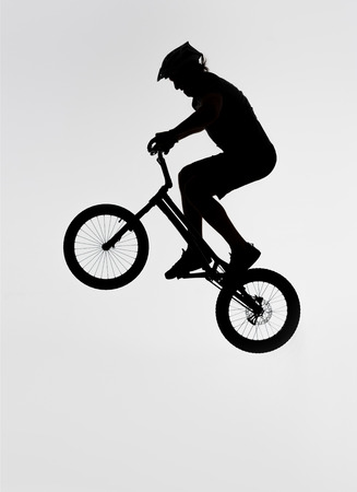 Silhouette of trial biker jumping on bicycle on white background