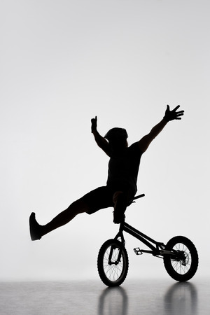 Silhouette of trial biker sitting on handlebars of bicycle on white background