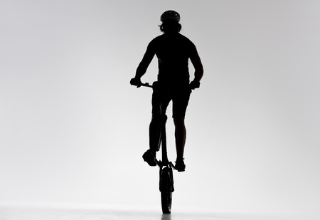 Silhouette of trial biker riding on back wheel on white background Stock Photo