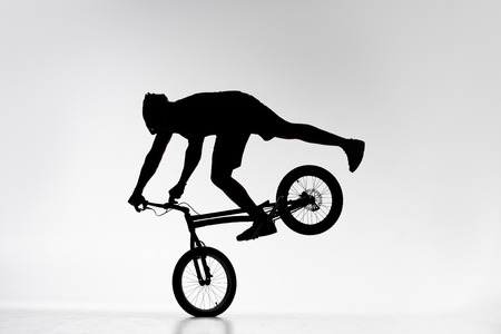 Silhouette of trial biker performing front wheel balancing stunt on bicycle on white background
