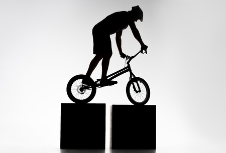 Silhouette of trial biker balancing on two stands on white background