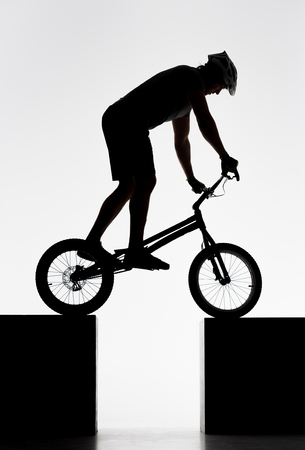Silhouette of trial cyclist balancing on two stands on white background