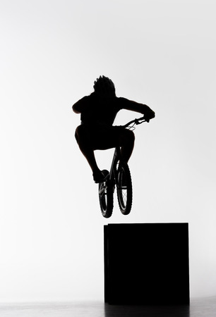 Silhouette of trial biker jumping on cube on white background