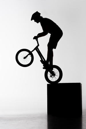 Silhouette of trial biker performing stunt while balancing on cube on white background Stock Photo