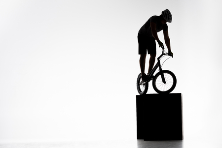Silhouette of trial cyclist balancing on obstacles on white background Stock Photo