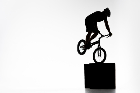 Silhouette of trial cyclist performing stunt while balancing on cube on white background Stock Photo