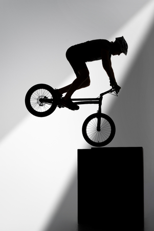 Silhouette of trial cyclist performing stunt while balancing on cube on grey background Stock Photo