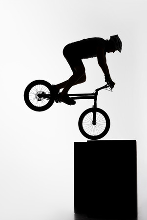 Silhouette of trial cyclist performing nollie while balancing on cube on white background