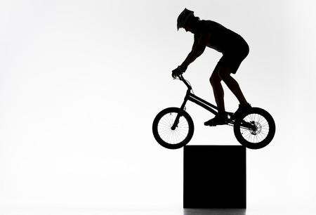 Silhouette of trial cyclist balancing on cube on white background Stock Photo