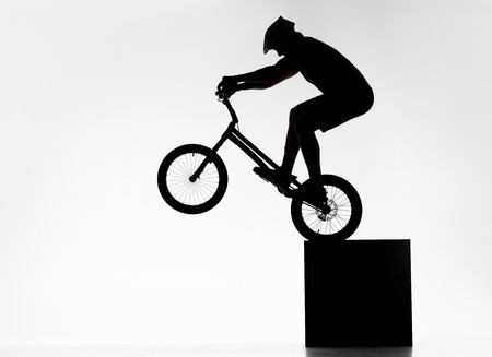 Silhouette of trial cyclist performing back wheel stand while balancing on cube on white background