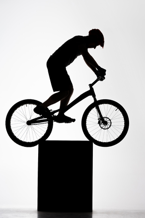 Silhouette of trial cyclist balancing on stand on white background Stock Photo